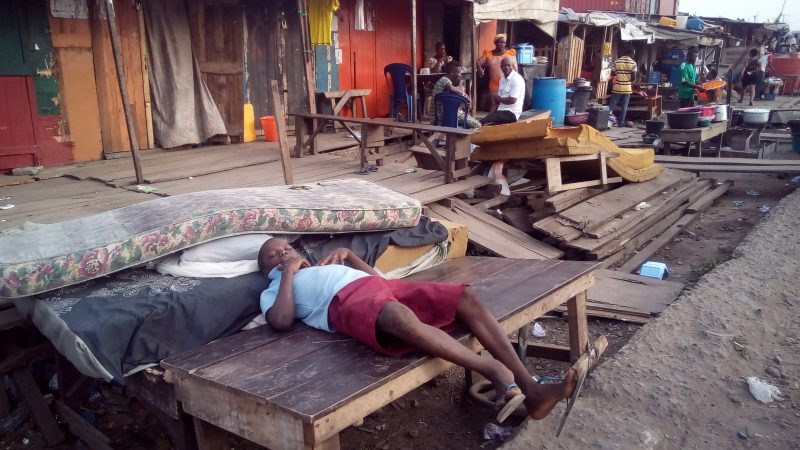 LAGOS BOY LYING DOWN IN FRONT OF THE RUBBLES OF HIS HOUSE